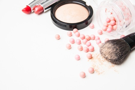 the bronzing pearls , lipstick and makeup brush. Isolated over white background. Standard-Bild
