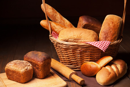 rollingpin: Composition with bread, rolls in wicker basket and cutting board and rolling-pin. Isolated on dark background. Stock Photo