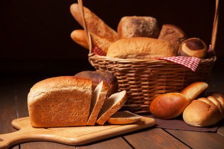 Composition with bread and rolls in wicker basket. Isolated over dark background. photo