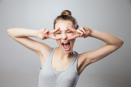 victory sign: Closeup portrait young attractive blonde woman, student, beautiful girl with v fingers across the face move, isolated grey background. Positive human emotions, face expressions, attitude