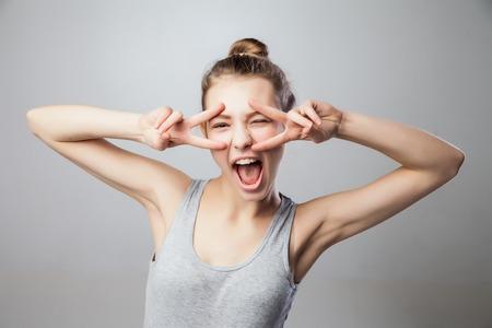 segno della pace: Ritratto del primo piano giovane donna attraente bionda, studentessa, bella ragazza con le dita contro tutto il movimento volto, isolato sfondo grigio. Emozioni umane positive, le espressioni del viso, atteggiamento Archivio Fotografico