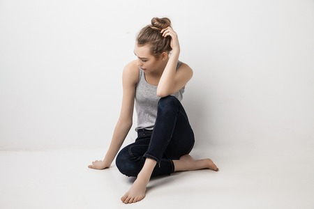 girl sitting down: Beautiful melancholic girl sitting on the floor and looking down. Isolated over grey background. Stock Photo