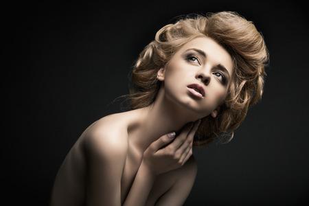 modelos posando: Modelo de mujer de alta moda hermosa con el peinado abstracto detrás de la mesa
