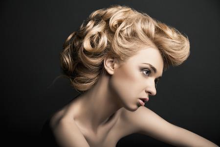 Modelo de mujer de alta moda hermosa con el peinado abstracto detrás de la mesa