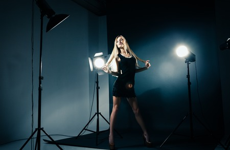 photography studio: Beautiful female model posing at studio in the light flashes