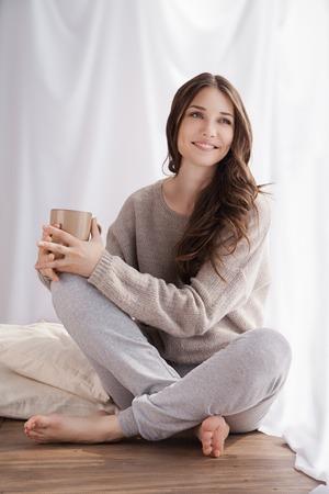 mooie vrouw het drinken koffie in de ochtend zitten bij het raam