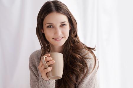 mujer tomando cafe: hermosa mujer de tomar café en la mañana sentado junto a la ventana