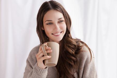 krásná žena pití kávy ráno sedí u okna