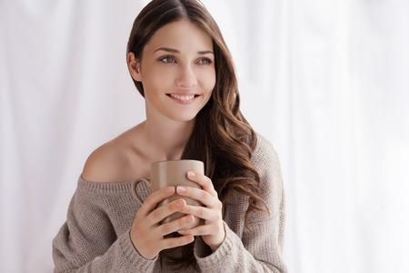 Bella donna bere caffè al mattino, seduta vicino alla finestra Archivio Fotografico - 36738240