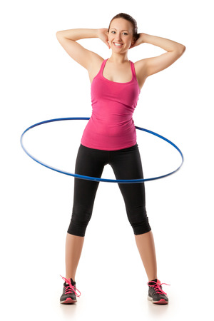fitness woman dressed in pink top and black leggins working with hoop smiling and holding her hands on head. Isolated over white Standard-Bild