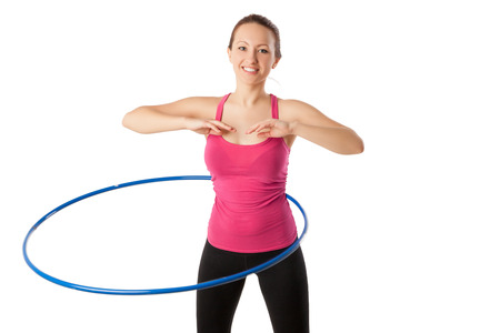 half dressed: fitness woman dressed in pink top and black leggins working with hoop smiling isolated over white. Half lngth view Stock Photo