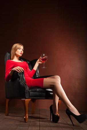 Portrait of a stunning fashionable model sitting in an armchair with wine glass. Business, elegant businesswoman. Interior, furniture. Standard-Bild