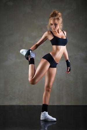 warm up: Fit donna si estende la gamba per riscaldare su sfondo grigio scuro Archivio Fotografico