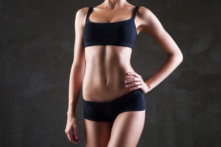 Slim tanned womans body  over dark grey background Standard-Bild