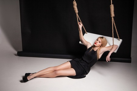 Beautiful young woman in stylish black dress and black shoes half-lying on swing in a studio photo