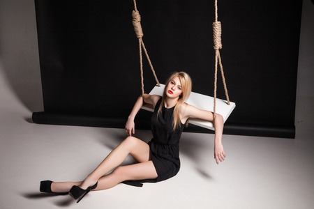 Beautiful young woman in stylish black dress and black shoes sitting on a floor by swing in a studio photo