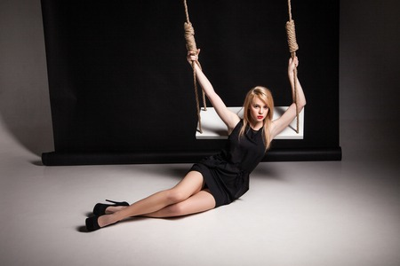Beautiful young woman in stylish black dress and black shoes posing on a floor by swing in a studio photo