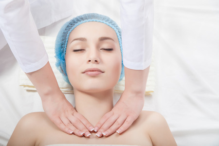 alternative medicine: Beautiful young woman undergoing a massage. Isolated over white background.