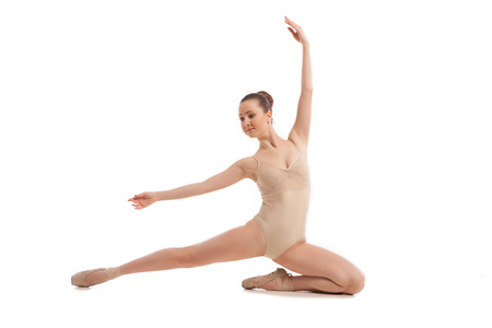 young pretty ballet dancer sitting in elegant pose isolated on white photo