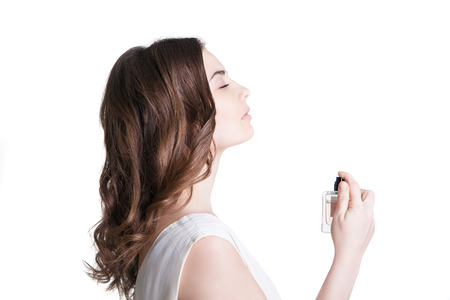 young woman spraying the perfume on her neck Standard-Bild