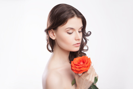 close-up portrait of beautiful brunette woman with red rose in her hand photo