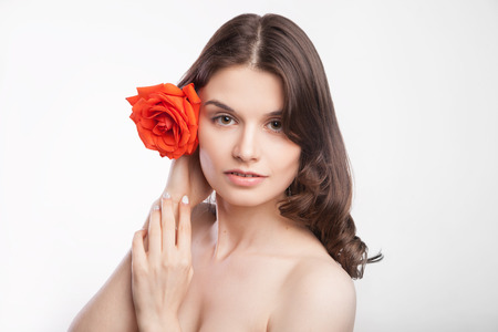 portrait of beautiful brunette woman with red rose in her hair photo