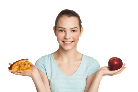 Young woman with a piece of pizza and apple, isolated on white photo