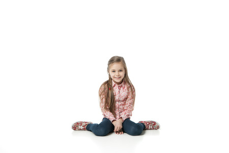 sitting on floor: Closeup image of a pretty little girl sitting on the floor in jeans. Isolated on white background