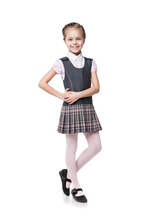 school year: Portrait of a beautiful little girl in school uniform isolated on white