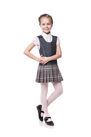 uniformes: Retrato de una hermosa niña en uniforme escolar aislado en blanco