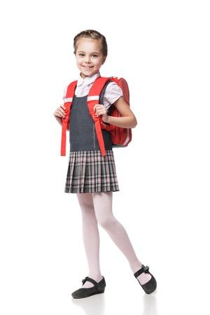 Volledige hoogte portret van een lachende schoolmeisje in uniform en met rugzak staande op een witte achtergrond Stockfoto