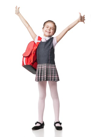 Pleine hauteur portrait d'une écolière en uniforme et heureuse avec sac à dos debout sur fond blanc