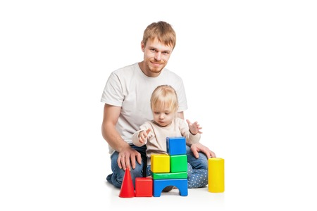 Down Syndrome: Baby girl building from toy blocks her father . Isolated on white background