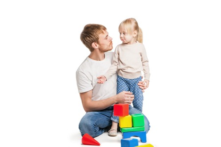 Baby girl building from toy blocks her father . Isolated on white background