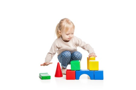 Baby girl building from toy blocks. Isolated on white background Standard-Bild