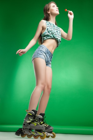 sexy lollipop: Very attractive woman with lollipop in sexy outfit posing on green studio background wearing inline rollerskates Stock Photo