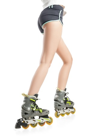blading: Close up  picture of womans legs with rollerskates isolated on white