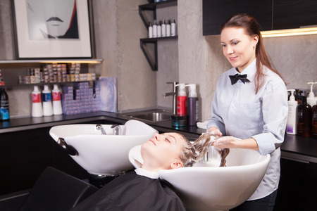 female in douche: Hairdresser washing a womans blond hair on saloon