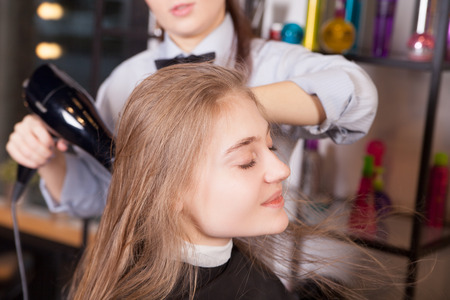 dry hair: Hairstylist drying blond hair by hairdryer in salon