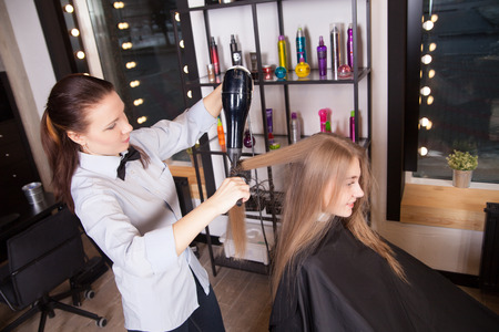 Hairstylist drying blond hair by hairdryer in salon