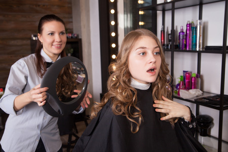 happy client: Happy client looking at mirror in salon. Stylist standing  behind the chair Stock Photo