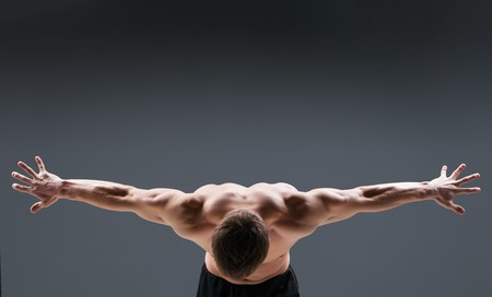 nude male body: Muscular young man in studio on dark background shows the different movements and body parts. Back view Stock Photo