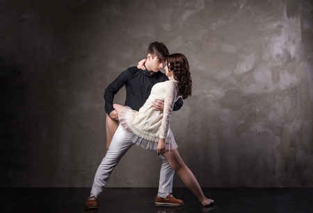 Beautiful couple in the active ballroom dance on dark background