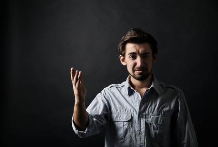 displeased: Displeased young man gesturing with one hand on black background