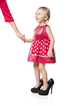 big shoes: Smiling little girl wearing big shoes kipping hand of her mother. Isolated on white background Stock Photo