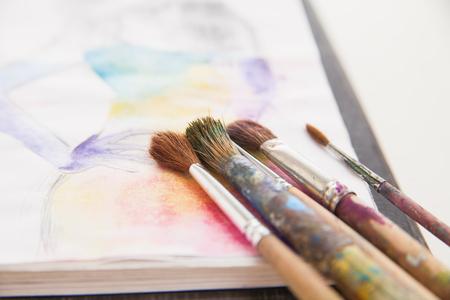 brocha de pintura: pinceles mienten en el fondo pintado colorido Foto de archivo