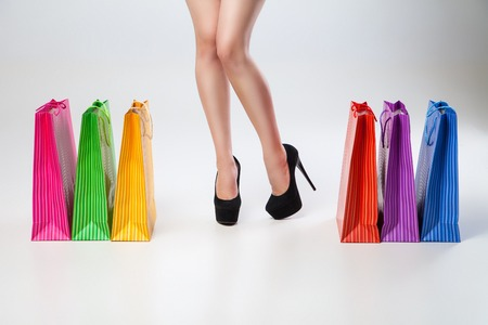 in vouge: Female thin legs colored bags posing over gray background