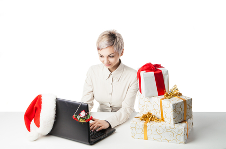 typ: Pretty young lady sitting at desk typing on laptop with present boxes and winter hat over white background