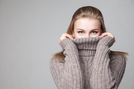 Hermosa joven rubia lleva jersey de invierno sobre fondo gris Foto de archivo - 49556584