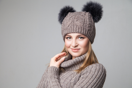 Beautiful blond young girl wears winter pullover and hat over gray background